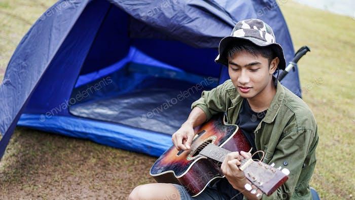 traveller man playing guitar at camp
