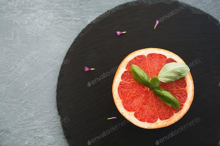 Grapefruit Hälfte auf schwarzem Schiefergrund