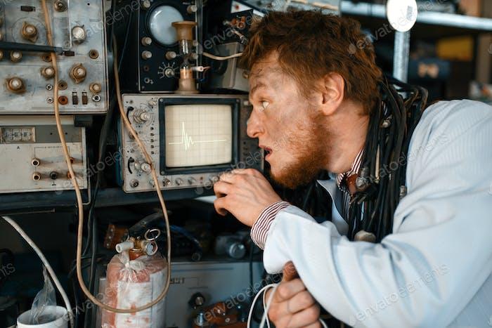 Engineer looks on oscilloscope display in lab