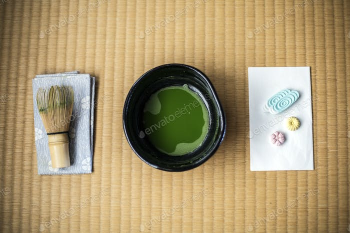Tea ceremony utensils including bowl of green Matcha tea, a bamboo whisk and Wagashi sweets.