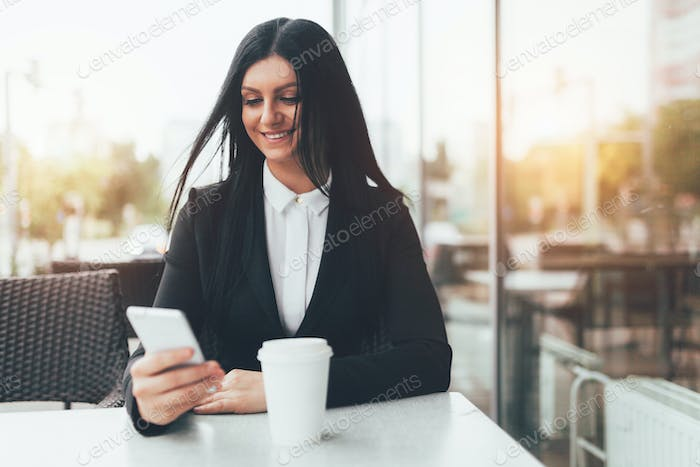 Business woman with smart phone sitting in a cafe