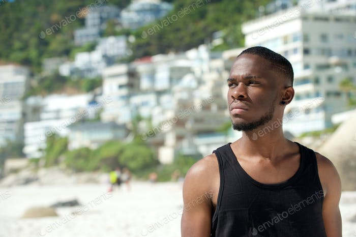 Handsome young man in black shirt standing at the beach