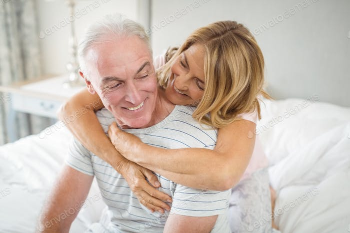 Happy senior couple embracing each other on bed