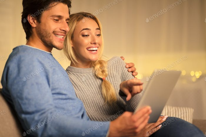 Happy couple searching gifts for christmas on tablet