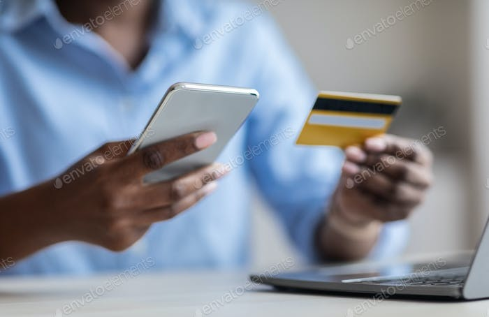 Money Transfers. Unrecognizable Black Businesswoman Using Smartphone And Credit Card For Payments