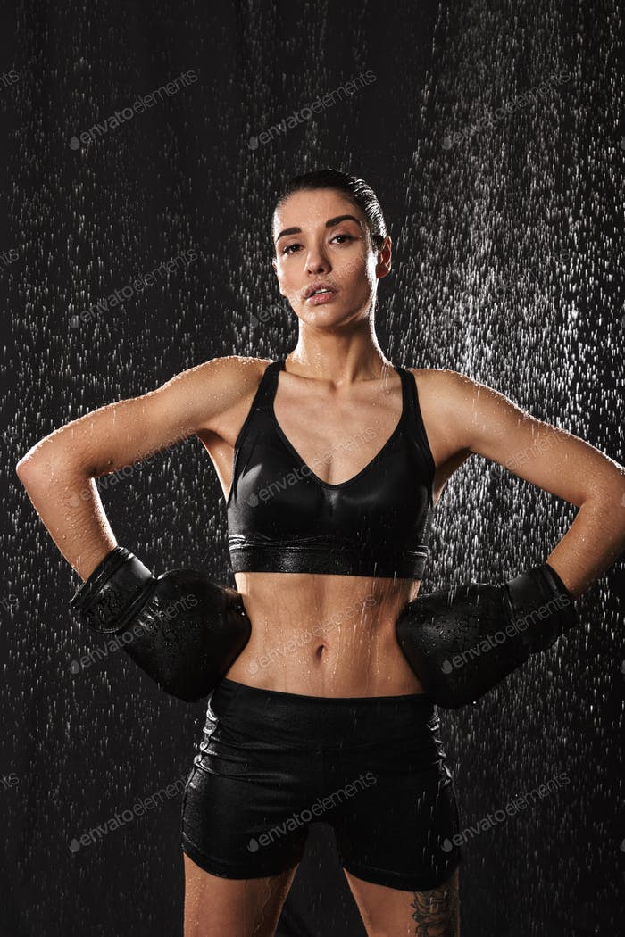 Wet sexual woman putting arms in boxing gloves on waist and look