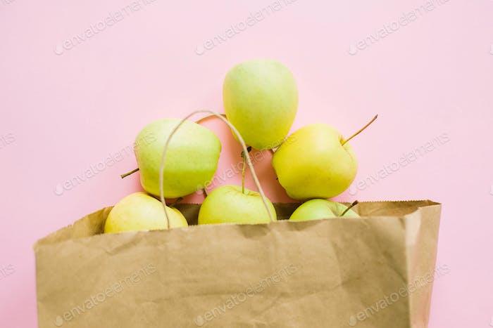 Äpfel in Papiertüte auf rosa Hintergrund