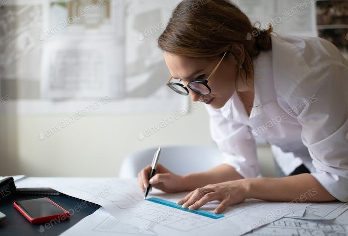 Smart businesswoman drawing blueprint in office