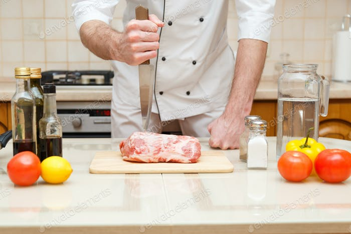 Butcher cutting meat on chopping board, professional cook holding knife and cutting meat.