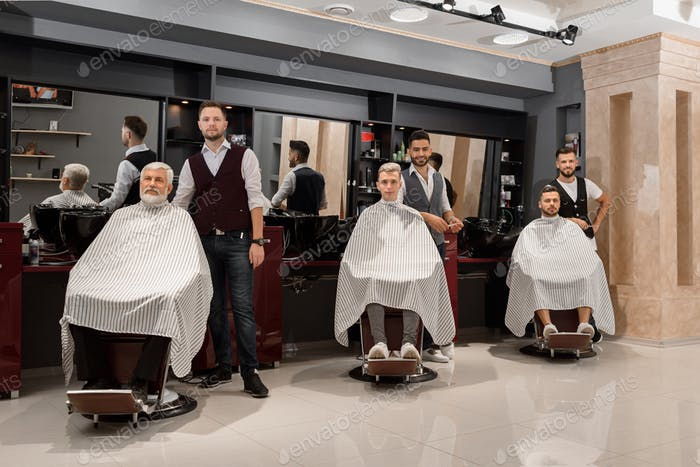 Barbers standing near clients covered with capes and sitting in hairdresser chairs