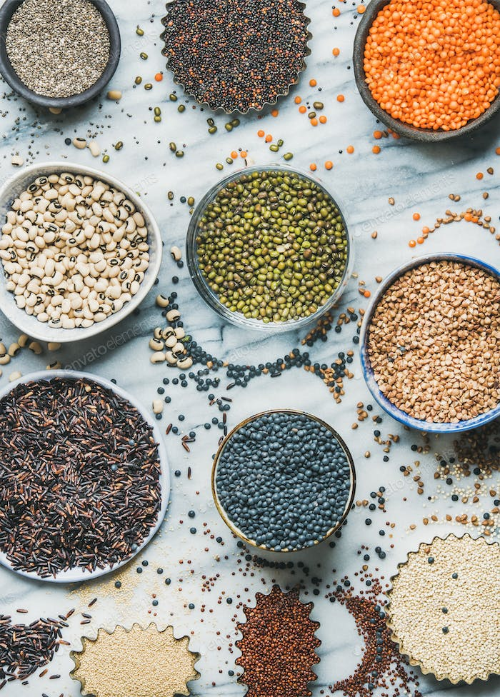 Various raw uncooked grains, beans, cereals in bowls, top view