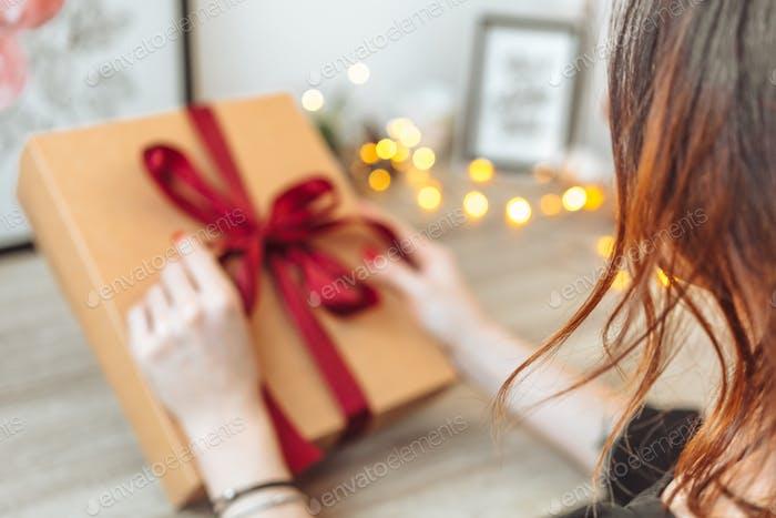 Frau Verpackung Geschenk in Papier mit rotem Band.