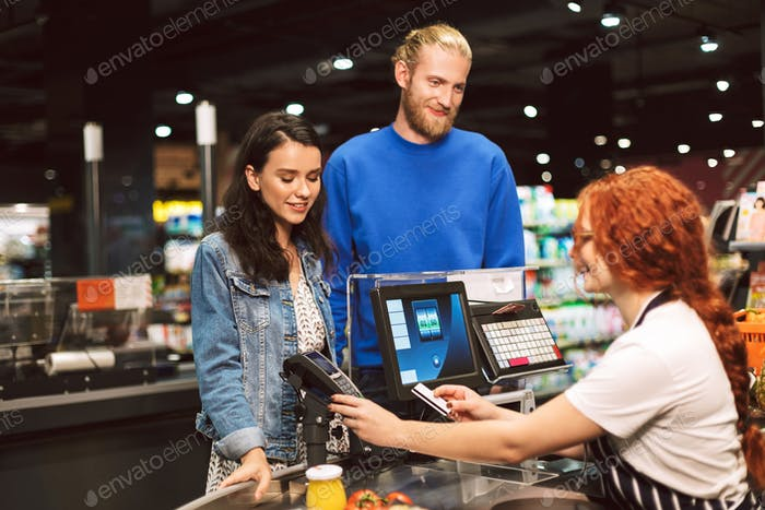 Young smiling couple standing near cashier desk while happily pa