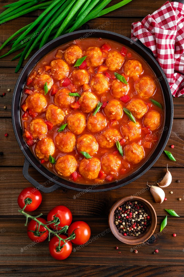 Chicken meatballs in spicy tomato sauce with vegetables in pan. Mexican cuisine