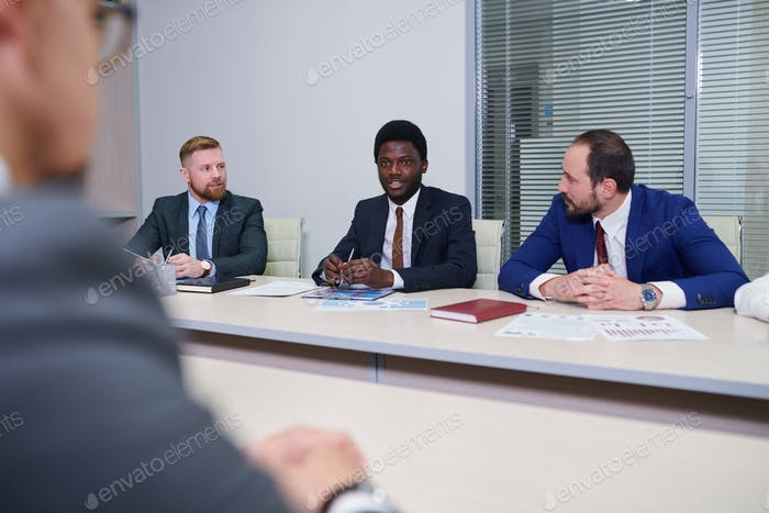 Group of contemporary traders listening to their African colleague