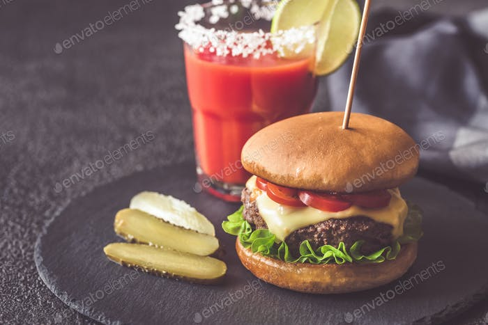 Hamburger with a glass of tomato juice