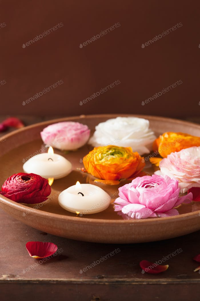 ranunculus flowers and candles in bowl for spa
