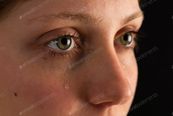 Face of unhappy female in tears from close up in darkness