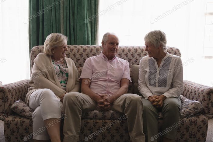 Front view of senior people interacting with each other in living room at home