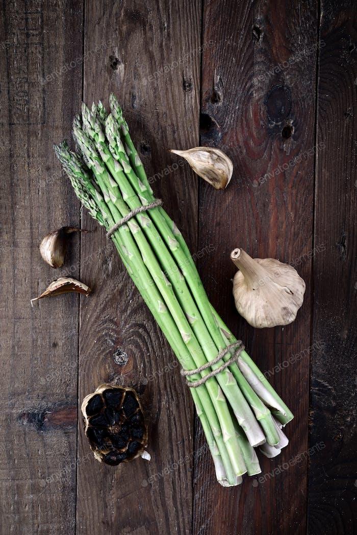 raw asparagus and black garlic, in wood