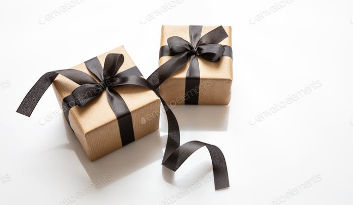 Gifts with black ribbon isolated against white background, Black Friday concept.