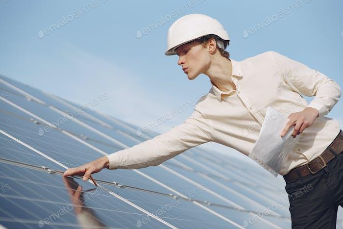 Geschäftsmann in einem weißen Helm in der Nähe von Solarbatterie