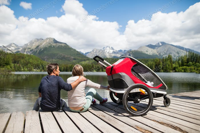 Senior couple with jogging stroller, summer day.