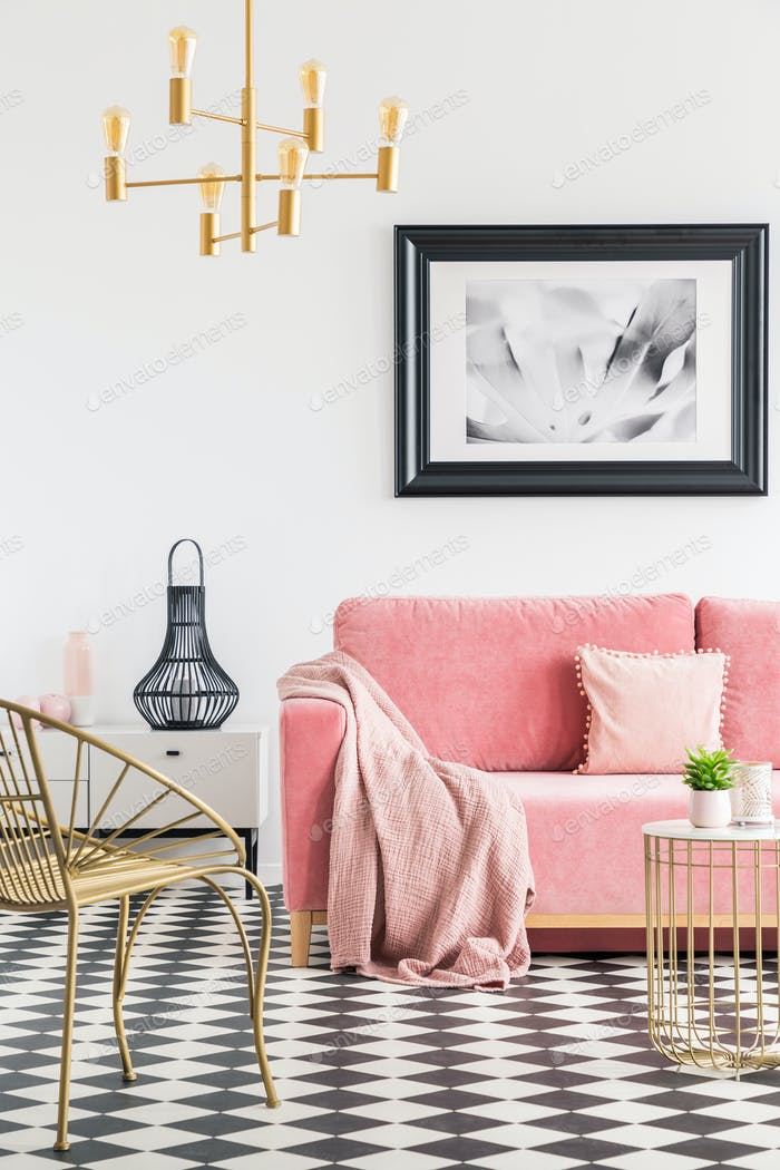 Poster above pink sofa with blanket in living room interior with