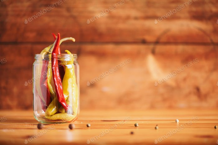 Probiotics food background. Pickled hot pepper chili in glass jars on wooden white background. Copy
