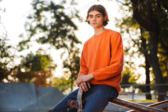 Young serious skater in orange pullover thoughtfully looking in
