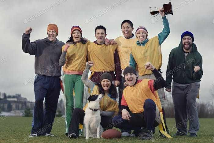Team members celebrating a victory and a trophy in an outdoor sporting event in the winter.