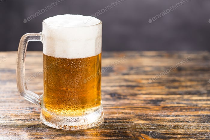 Cold glass of lager beer on wooden table