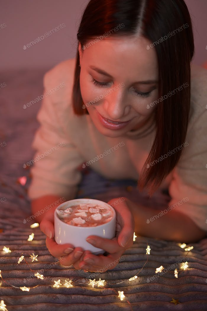 Lovely woman lying on bed with glowing lights