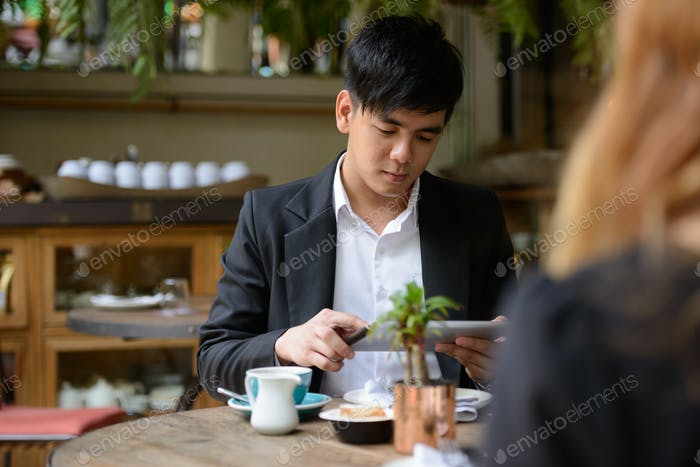 Young Asian business couple together at the coffee shop with man using digital tablet