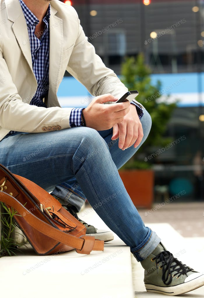 Man sitting outdoors on steps with mobile phone