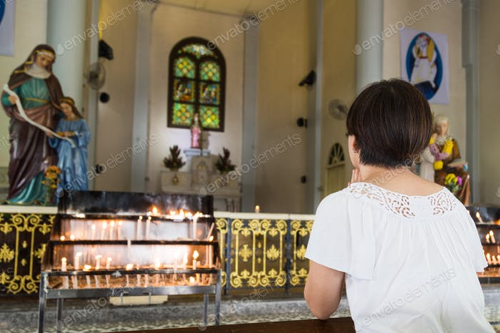 Believer kneel and praying in a Catholic church