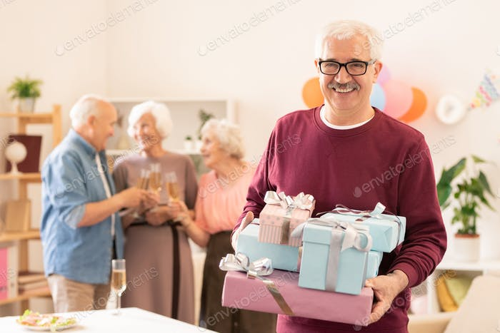 Joyful mature man with several giftboxes