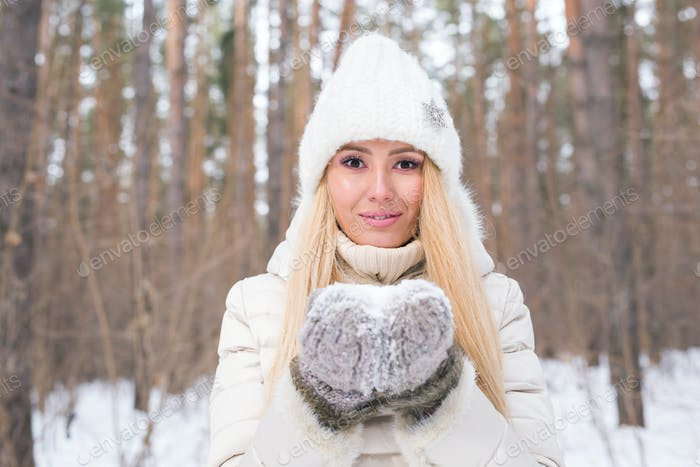 Christmas, holidays and season concept - Young happy blond woman blowing snow in the winter nature