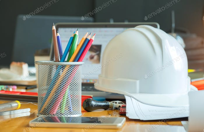 Multi colored pencils in box with safety helmet,smart phone.
