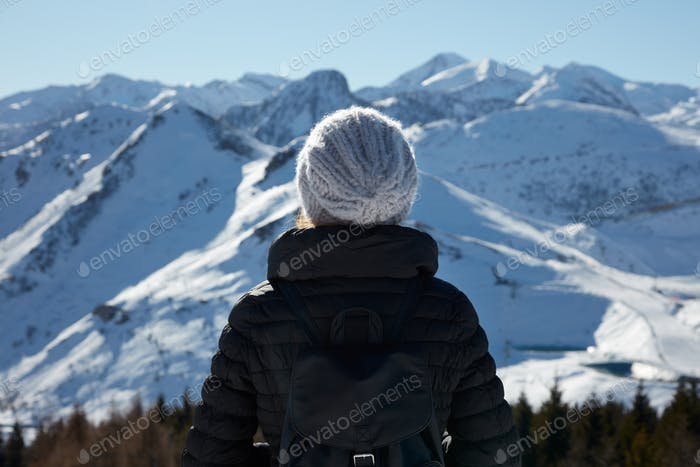 Woman with wool hat looking at mountains with snow in a sunny day