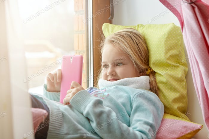 Happy little girl of European appearance using mobile phone indoors, looking at screen with interest