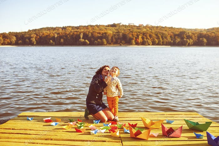 Mom and son playing with paper boats by the lake