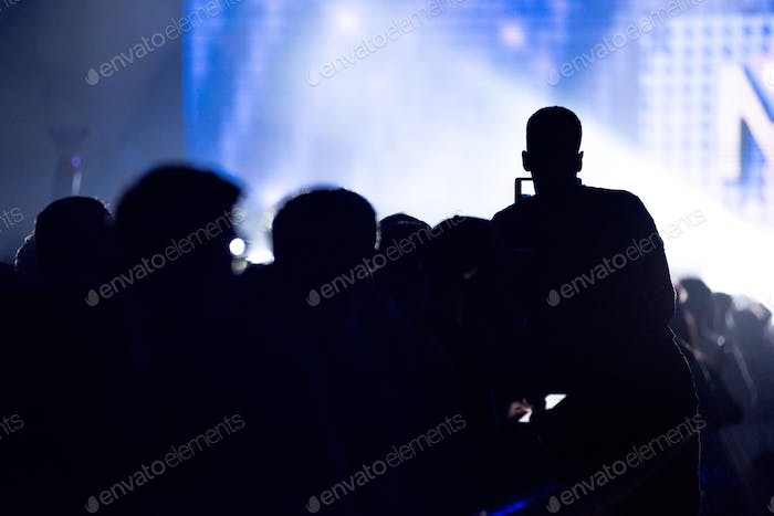 Silhouette of Raised Hands Holding a Smart Phone Recording Music Concert