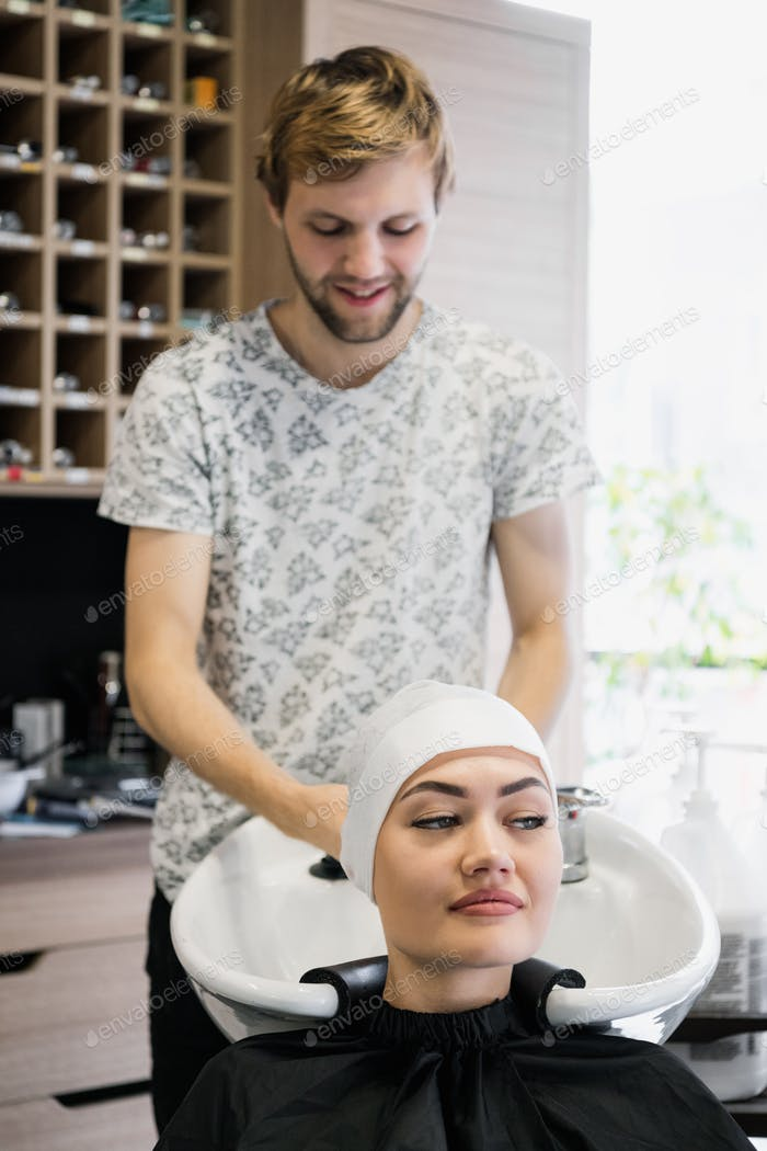 Hairdresser wrapping towel on customer's head. Brunette woman getting hair treatment in a salon.
