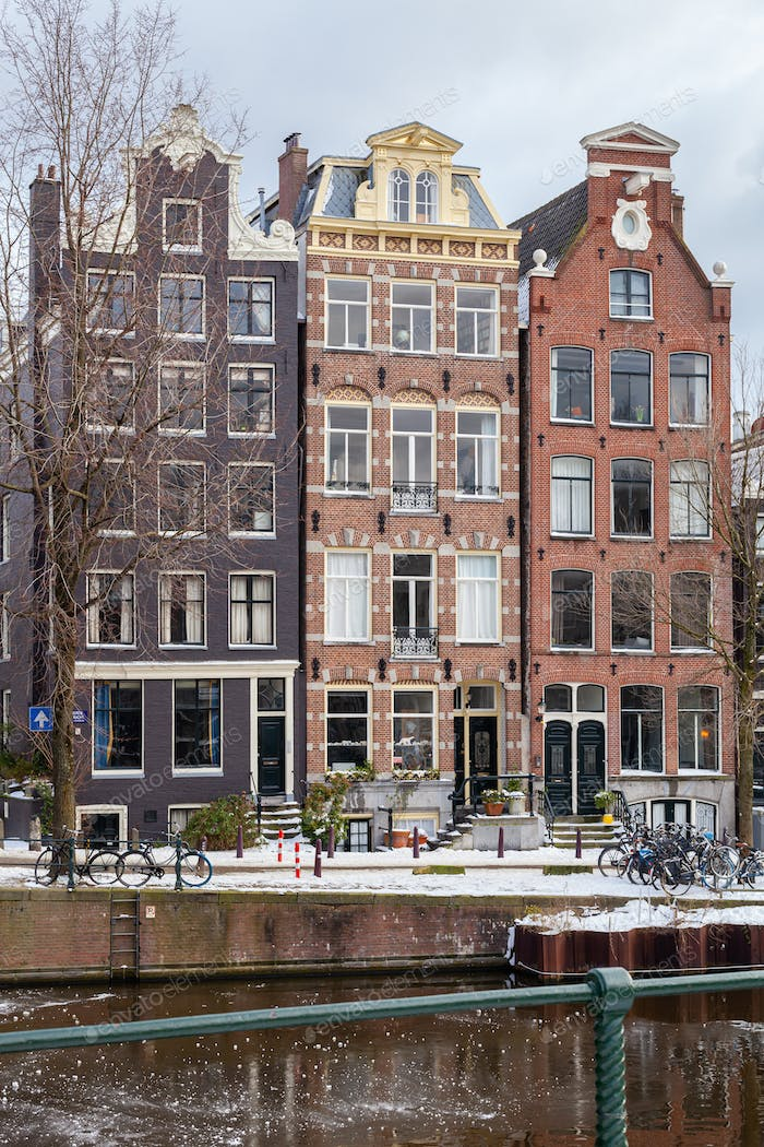A winter scene of Amsterdam canal houses in the snow with ice on the water, capital