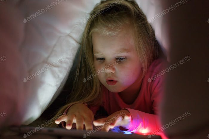 Little girl is playing on the tablet in secret from her parents at night under the blanket.