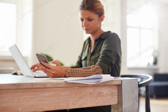 Woman at home office using mobile phone
