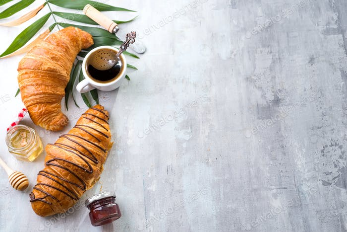 freshly baked croissant and cup of coffee decorated with chocolate sauce and palm leave