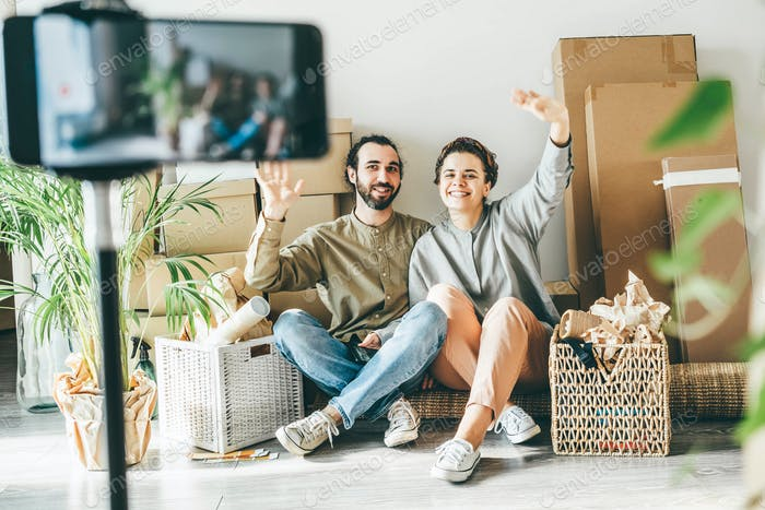 couple with belongings sits on floor filming video in new apartment