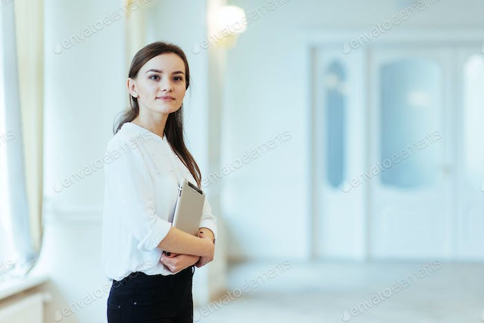 Smiling business woman holding a tablet computer at the office